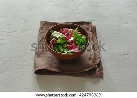 bowl of fresh salad on a white surface. Concept helpful and simple food - stock photo
