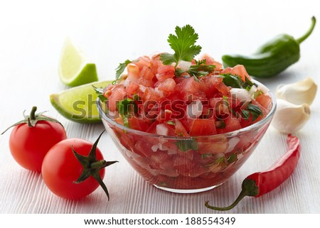 Bowl of fresh salsa dip and ingredients on white wooden background - stock photo