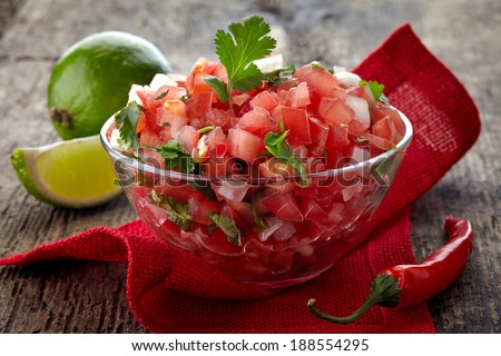 Bowl of fresh salsa dip on wooden background - stock photo
