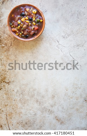 Bowl of fresh salsa on stone surface with copy space and viewed from above. - stock photo