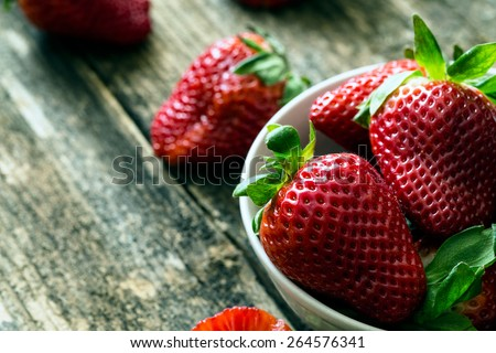 bowl of fresh strawberries on old wooden table