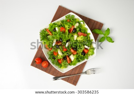 bowl of fresh vegetable salad on brown place mat - stock photo