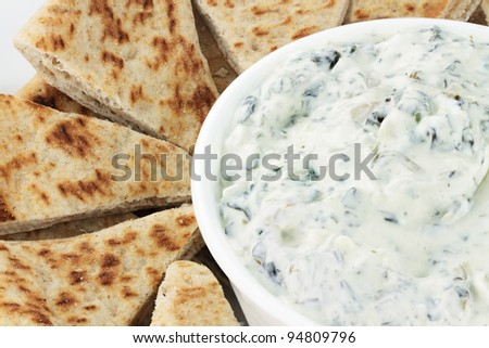 Bowl of fresh vegetarian spinach dip served with wedges of pita bread for a healthy snack. - stock photo