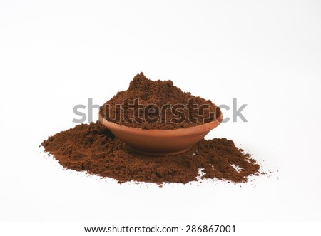 bowl of freshly ground coffee on white background