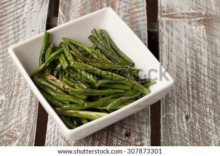 Bowl of freshly harvested Asian green beans on a weathered barn wood table cooked and ready to serve - stock photo