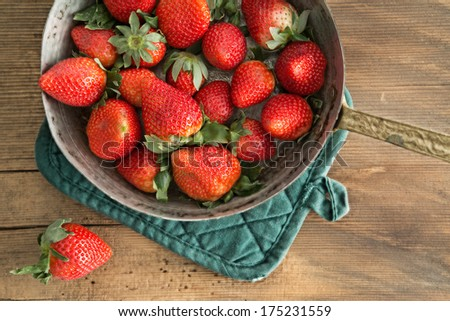 Bowl of freshly harvested ripe red strawberries waiting on a wooden kitchen counter to be made into jam, over head view - stock photo
