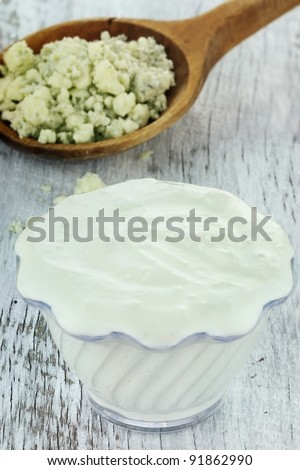 Bowl of freshly made blue cheese salad dressing with chunks of blue cheese in wooden spoon on a rustic background.