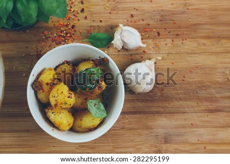Bowl of freshly prepared garnished organic potatoes on a vintage wooden table. Retro styled imagery, grain added - stock photo