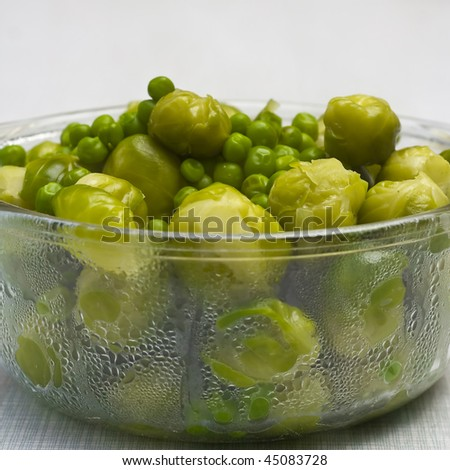 Bowl of freshly steamed peas and vegetables - stock photo