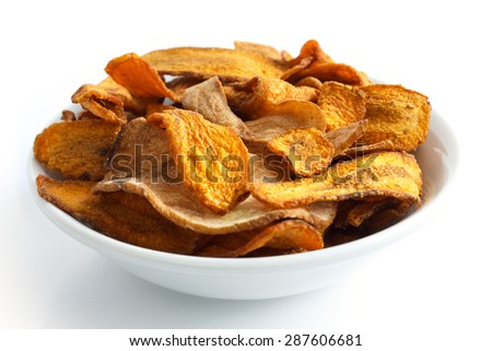 Bowl of fried carrot and parsnip chips. Isolated.