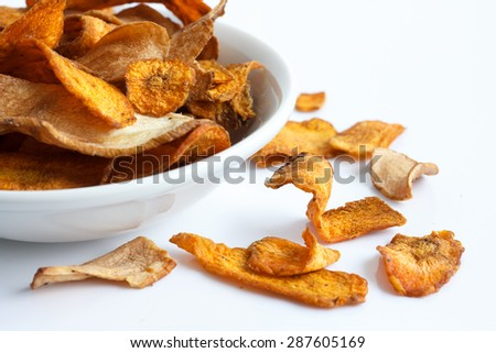 Bowl of fried carrot and parsnip chips. On white.