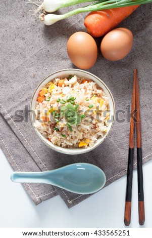 Bowl of fried rice, carrot and egg on pink fabric, spoon, chopsticks and ingredients for background