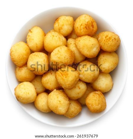 Bowl of fried small potato balls on white. - stock photo