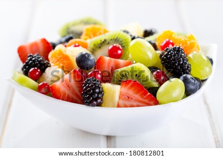 bowl of fruit salad on wooden table - stock photo