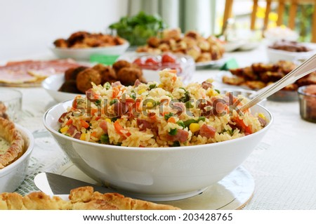 Bowl of gammon and mixed vegetable rice salad with other party food on a buffet table - stock photo