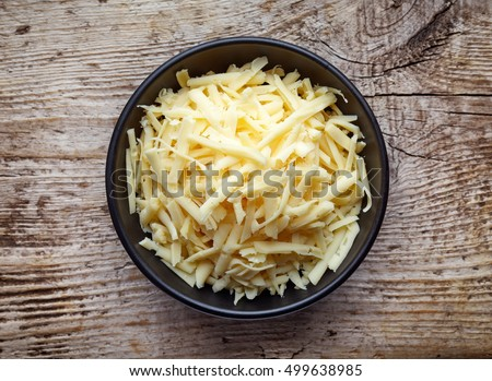 Bowl of grated cheese on wooden background. top view