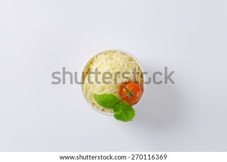 bowl of grated parmesan cheese, cherry tomato and basil on white background - stock photo