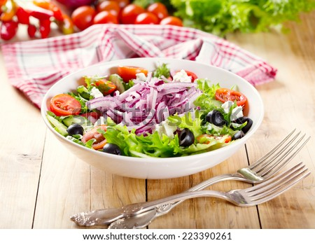 bowl of greek salad on wooden table - stock photo
