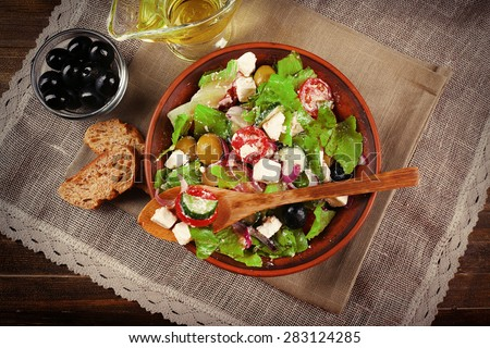 Bowl of Greek salad served on napkin on wooden background closeup - stock photo