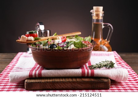 Bowl of Greek salad served with olive oil on napkin on wooden table on dark background