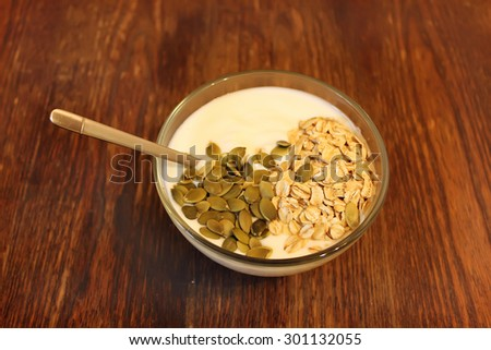 Bowl of greek yogurt with oatmeal and seeds on wooden table - stock photo
