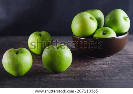 Bowl of green apples and apple over wooden board - stock photo