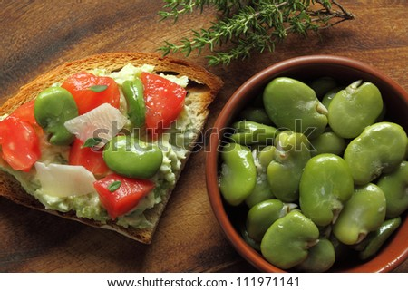 Bowl of green boiled broad beans and sandwich - stock photo