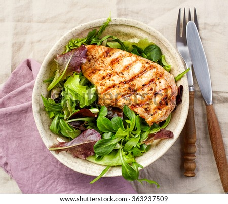 Bowl of green salad and grilled chicken fillet, top view - stock photo