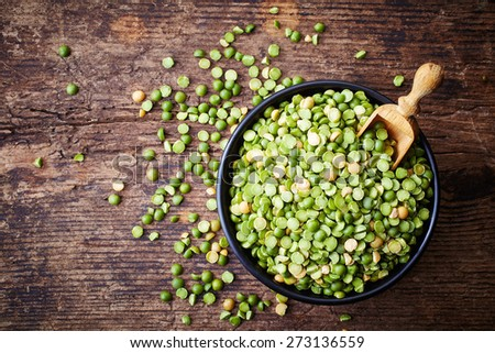 Bowl of green split peas on wooden background - stock photo