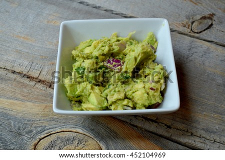 Bowl of guacamole on rustic wood table - stock photo