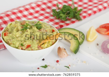 Bowl of guacamole with fresh ingredients on a white table