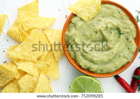 Bowl of guacamole with tortilla chips on white background