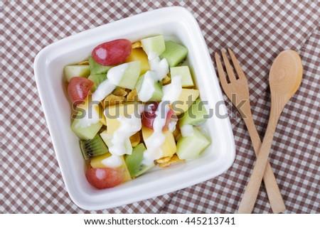 Bowl of healthy fresh fruit salad with yogurt. Top view. - stock photo