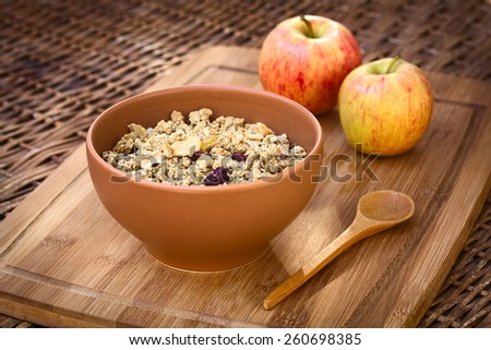Bowl of healthy oatmeal cereal with almonds, dried apple and cranberries photographed with natural light (Selective Focus, Focus in the middle of the granola) - stock photo