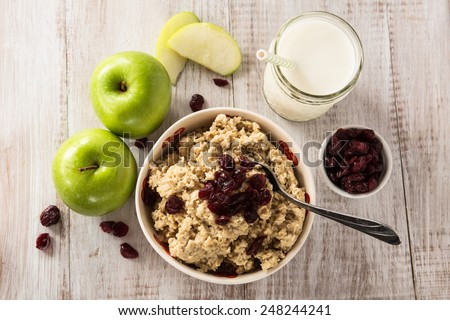 Bowl of heart healthy breakfast oatmeal with apples and cranberries and glass of milk - stock photo