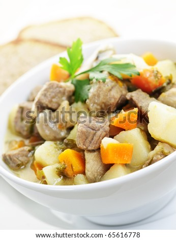 Bowl of hearty beef stew with vegetables served with rye bread - stock photo