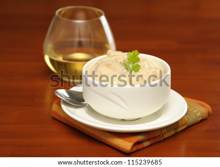Bowl of hearty clam chowder served with white wine. - stock photo
