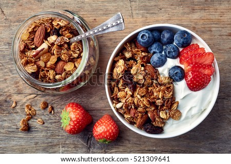 Bowl of homemade granola with yogurt and fresh berries on wooden background from top view