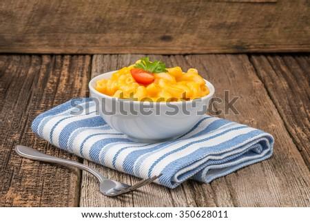Bowl of homemade macaroni and cheese with garnish. - stock photo