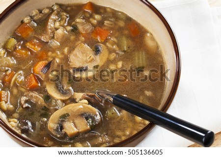 Bowl of homemade mushroom and barley soup with spoon in it ready to eat