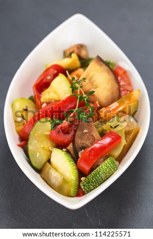 Bowl of homemade Ratatouille made of eggplant, zucchini, bell pepper and tomato and seasoned with herbs (garlic, thyme, oregano) (Selective Focus, Focus on the front leaves of the thyme on the meal)
