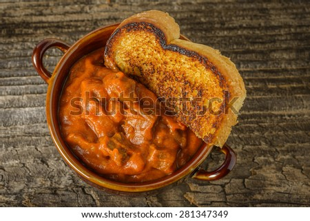 Bowl of homemade steak chili served with toast. - stock photo