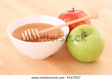 bowl of honey with wooden stick and apples on table