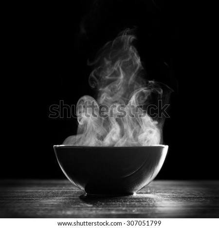 Bowl of hot soup on black background - stock photo