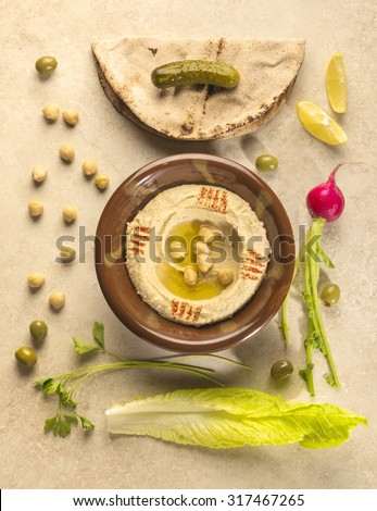 Bowl of Hummus - a popular arabic starter dish arranged artistically along with raw ingredients, green vegetables, kuboos and fried falafel. Top view angle.  - stock photo