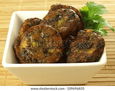Bowl of indian appetizer: spinach pakoras, closeup - stock photo