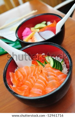 Bowl of Japanese salmon don (sushi rice) topped with salmon roe, and a bowl of mixed sashimi don - stock photo