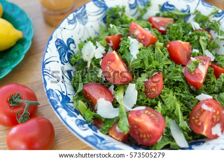 Bowl of Kale and Tomato Salad with Parmesan Cheese Shavings.