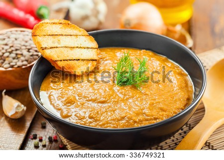 Bowl of lentil cream soup with toasts on kitchen table