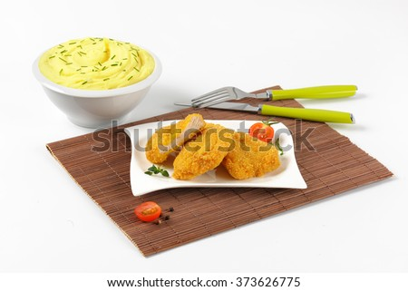 bowl of mashed potato puree with chopped chives and plate of breaded turkey breast on brown place mat - stock photo